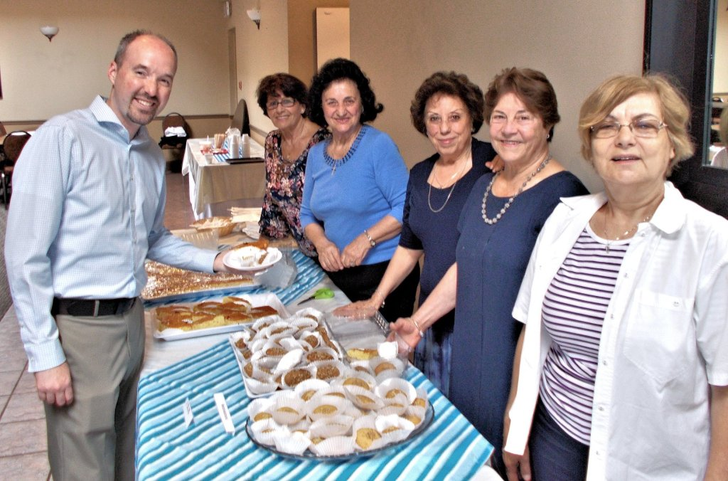 """Some members of Philoptohos in June 2018 as they sold Greek pastries at """"Doors Open Kingston"""" to many visitors, including Mayor Bryan Paterson."""