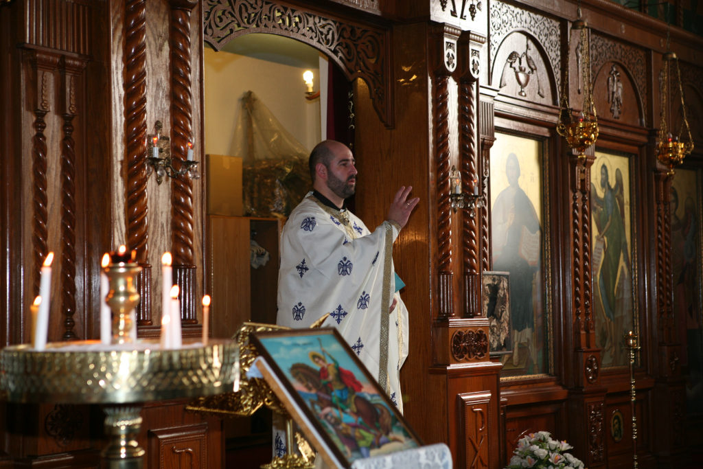 """Fr. C. in Kingston's Greek Orthodox Church. We can see the intricately decorated walls of the church, and the """"visual splendor"""" of everything from the icons to the Priest's vestments."""